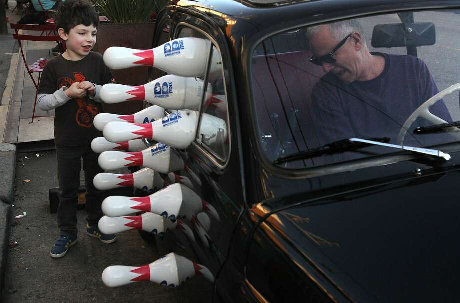 Eric Staller's Big Bang Theory, a 1970 Fiat 500 with 10 bowling pins on the door, catches the eye of Cole Kurin in S.F. Photo: Leah Millis, The Chronicle