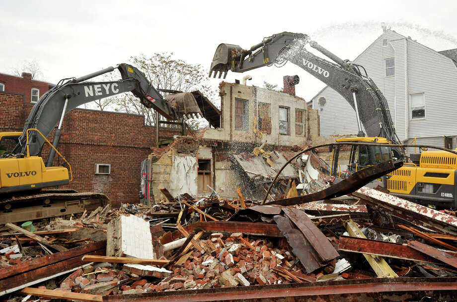 A demolition crew from New England Yankee Construction from Milford, Conn., work to take down a building at the corner of Myrtle Avenue and Elm Street in Stamford, Conn., on Monday, Jan. 20, 2014 to make way for a wider intersection. Photo: Jason Rearick / Stamford Advocate