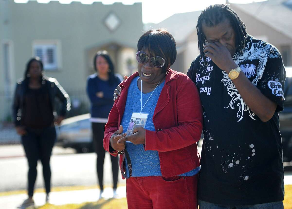Dinyal New (left) and Freddie New are seen at the site (100th and Longfellow) in Oakland where Dinyal's son Lamar Broussard and his friend Derryck Harris were killed last night. New's other son Lee Weathersby III was killed just weeks earlier on New Year's Eve.