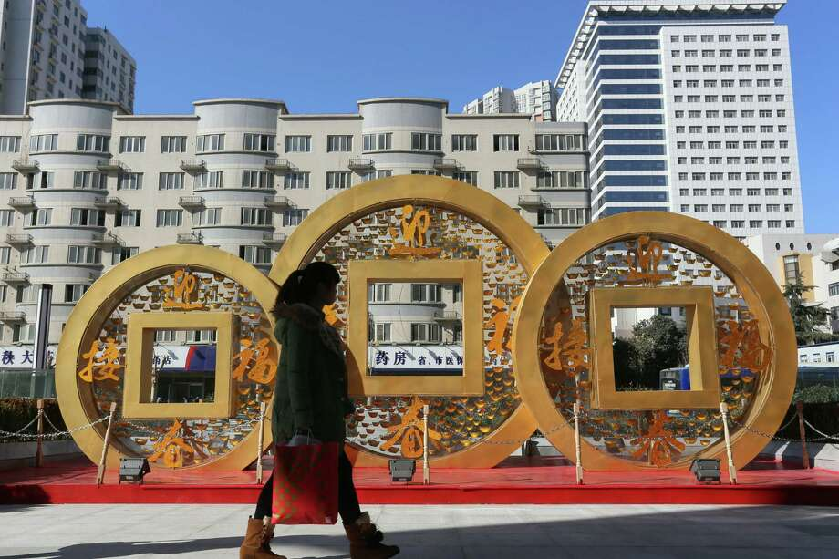 ZHENGZHOU, CHINA - JANUARY 20:  (CHINA OUT) People walk past a copper coin-shapped decoration for Chinese New Year on January 20, 2014 in Zhengzhou, China. China's economy expanded 7.7 percent year-on-year in 2013, according to the National Bureau of Statistics on Monday.  (Photo by ChinaFotoPress/ChinaFotoPress via Getty Images) ORG XMIT: 464361221 Photo: ChinaFotoPress / 2013 Getty Images