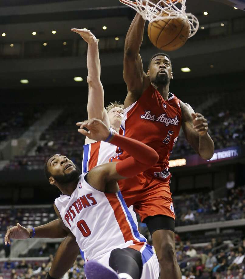 Clippers center DeAndre Jordan dunks over Detroit's Andre Drummond (0) and Kyle Singler for two of his 16 points. Photo: Carlos Osorio, Associated Press