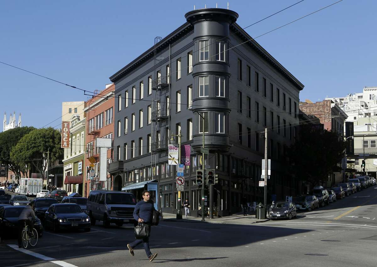 A pedestrian runs past a building painted black at Columbus Avenue and Kearny Street in San Francisco, Calif. on Tuesday, Jan. 14, 2014. Painting or covering buildings in dark gray or black is becoming very trendy throughout the city.