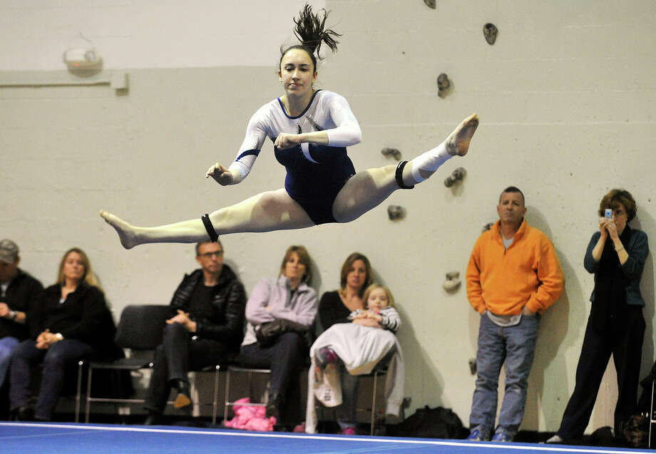 Staples' Deanna Baris leaps as part of her floor routine during her team's gymnastics meet against Greenwich at the YWCA in Greenwich, Conn., on Monday, Jan. 20, 2014. Photo: Jason Rearick / Stamford Advocate
