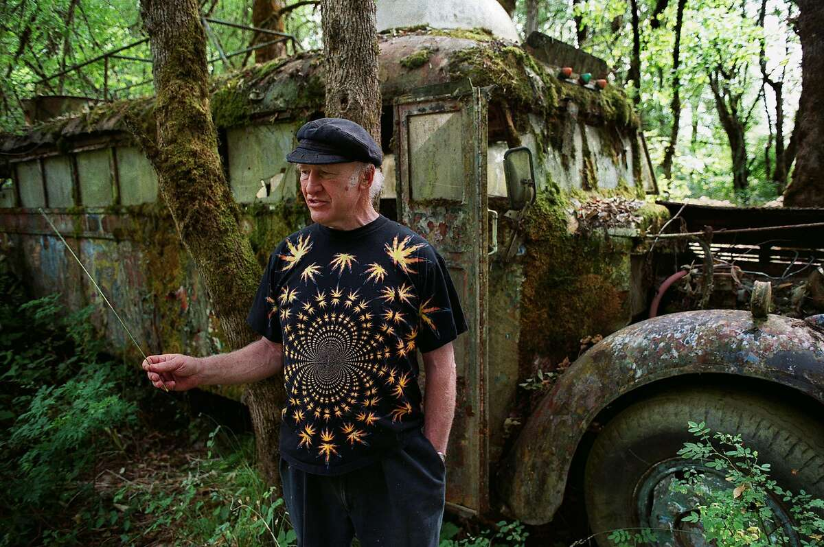 """Author Ken Kesey walks beside the original """"Furthur"""" bus, made famous in Tom Wolfe's 1968 book """"The Electric Kool Aid Acid Test"""" July 17, 2001 on his farm in Pleasant Hill, Ore. Kesey, who railed against authority in ``One Flew Over the Cuckoo's Nest'' and orchestrated an LSD-fueled bus ride that helped immortalize the psychedelic 1960s, died Saturday. He was 66. (AP Photo/The Register-Guard, Brian Davies) ALSO Ran on: 01-15-2006 Ken Kesey, holding a flute, rode on top of Furthur with some of the Merry Pranksters in 1967 during a rollicking trip to San Francisco from his home in La Honda."""