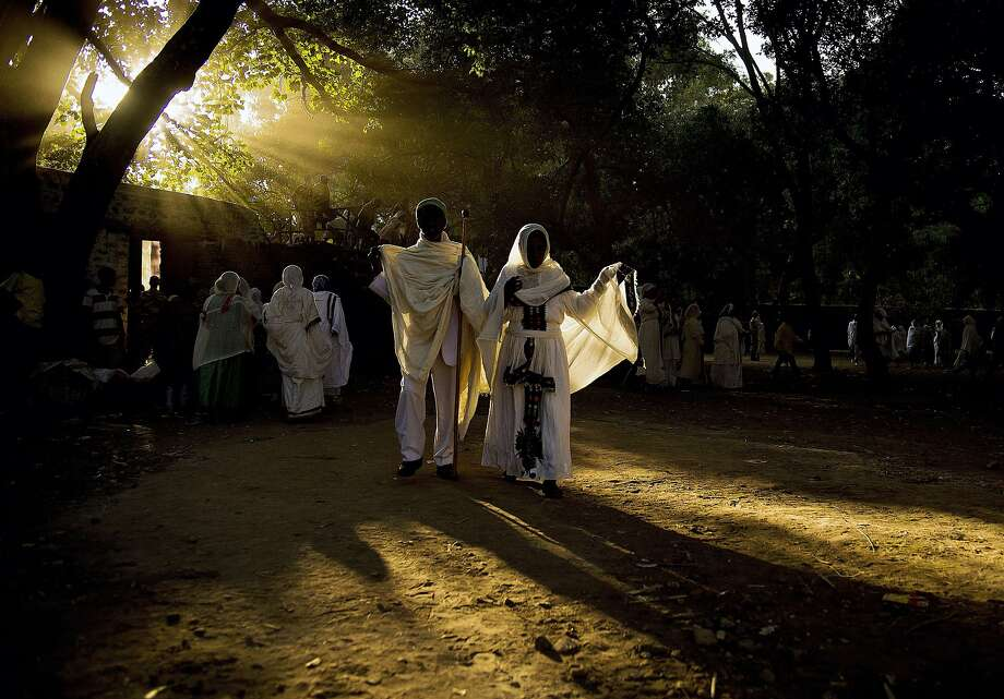 TOPSHOTS Ethiopian orthodox christians walk towards the Fasilides baths during the Timkat festival in Gondar on January 20, 2014. Timkat is the Ethiopian Orthodox Christian festival which celebrates the baptism of jesus in the Jordan river. During Timkat, Tabots, or models of the Ark of the Covenant are taken from churches and paraded through the streets.  AFP PHOTO / CARL DE SOUZACARL DE SOUZA/AFP/Getty Images Photo: Carl De Souza, AFP/Getty Images