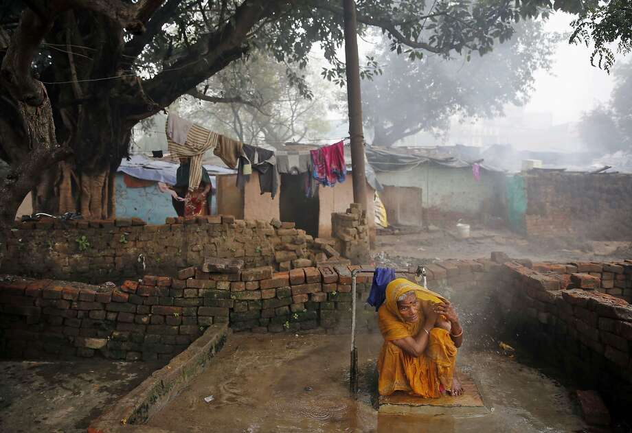 An Indian woman takes a cold shower at a municipality water place in a slum area in a cold foggy morning in Allahabad, India, Monday, Jan. 20, 2014. Dense fog enveloped few places over the state as cold conditions continue unabated, according to local reports. (AP Photo/Rajesh Kumar Singh) Photo: Rajesh Kumar Singh, Associated Press
