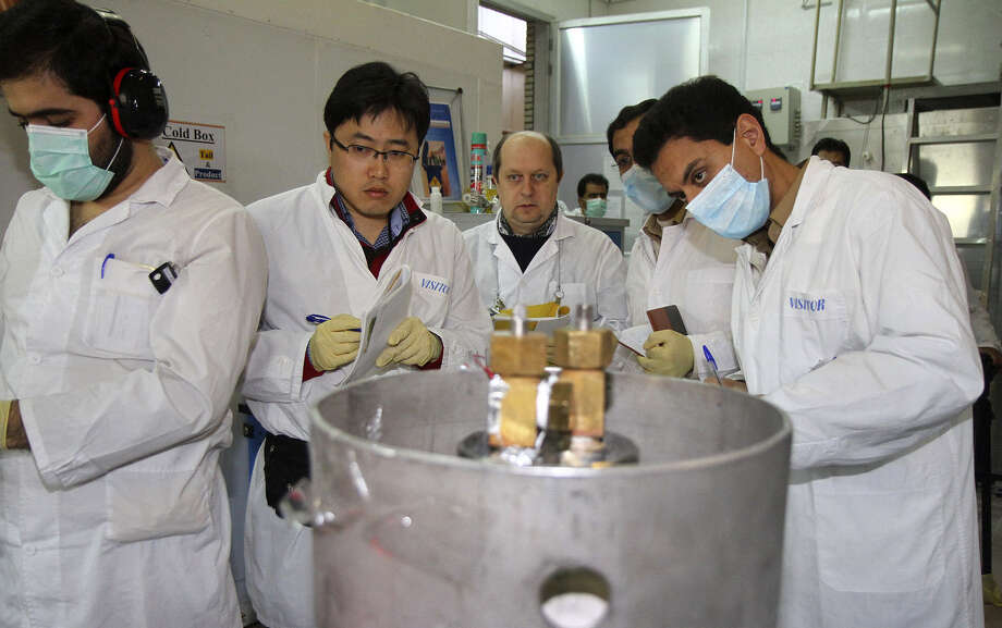 Nuclear inspectors and Iranian technicians prepare for the disconnection of centrifuge cascades at the Natanz nuclear facility. Photo: Kazem Ghane / IRNA / Associated Press / Islamic Republic News Agency, IR