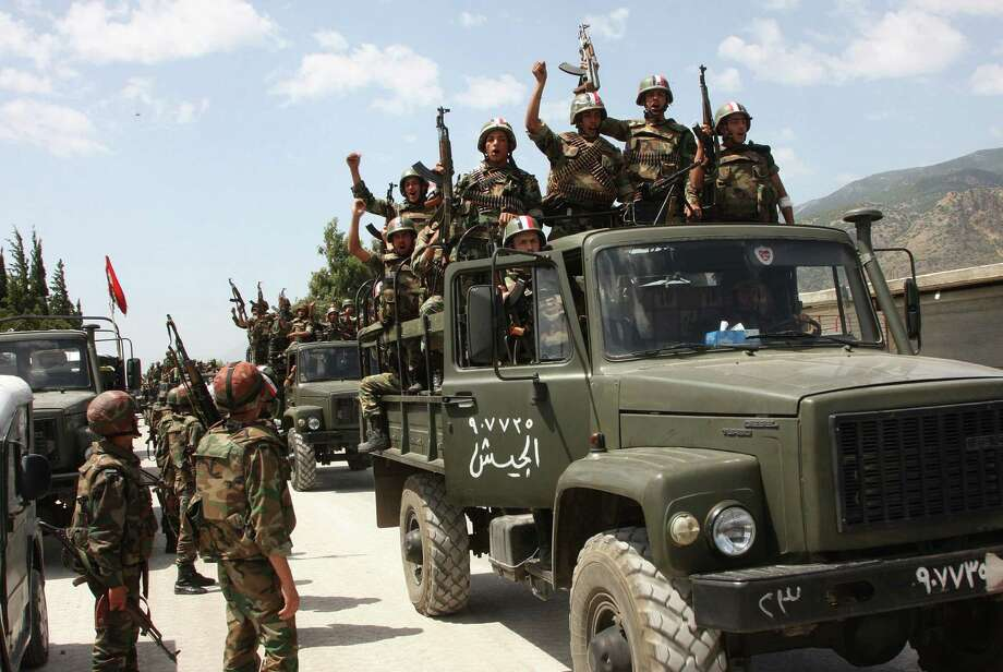Syrian soldiers shout slogans of support for Syrian President Bashar Assad as they enter a village near the town of Jisr al-Shughour in 2011. Assad said he likely would seek a new term in June. Photo: Associated Press File Photo / AP