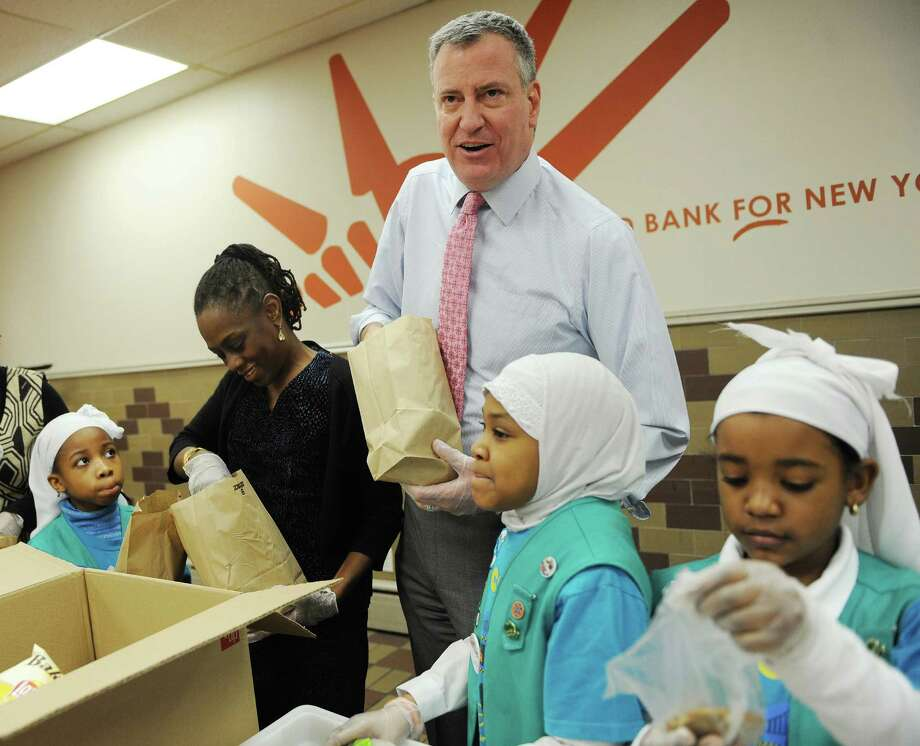 Mayor Bill de Blasio, center, and New York City's first lady, Chirlane McCray, mark the Martin Luther King Jr. holiday by bagging meals with Girl Scouts from Brooklyn Troop 2260 at the Distribution Community Kitchen and Food Pantry in run by New York's Food Bank the Food Bank in New York's Harlem neighborhood  Monday Jan. 20, 2014. According to Food Bank officials, 2.6 million New Yorkers face difficulty feeding themselves — a number that is rising as food supplies drop and food costs rise.  (AP Photo/New York Daily News, Susan Watts, Pool) ORG XMIT: NYNYD101 Photo: Susan Watts / Pool New York Daily News