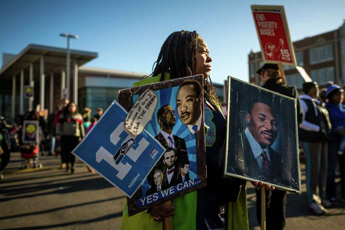 """Fai Mathews, 61, gathers an armful of signs while preparing to walk the 32nd ?'Rise Up! Restore the Dream!?"""" annual celebration for Martin Luther King, Jr., on Monday, Jan. 20, 2014, in Seattle. Mathews' portrait of MLK, in her left hand, has been in her family for 30 years. A mass of hundreds walked from Garfield High School to Westlake Park. The event also included a rally and a workshop."""
