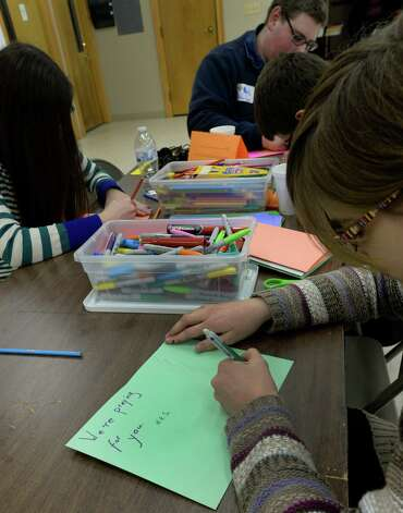 Niamah Schmid of Howes Cave, foreground, joined by other young adults as they make inspirational cards for the Phillipine Islands which were hit by typhoon haiyan  Monday afternoon Jan. 20, 2014 in Middleburgh, N.Y.  as part of the Dr. Martin Luther King, Jr. Day of Reflection on Service: Stories of Hurricane Irene program.        (Skip Dickstein / Times Union) Photo: SKIP DICKSTEIN / 0025433A