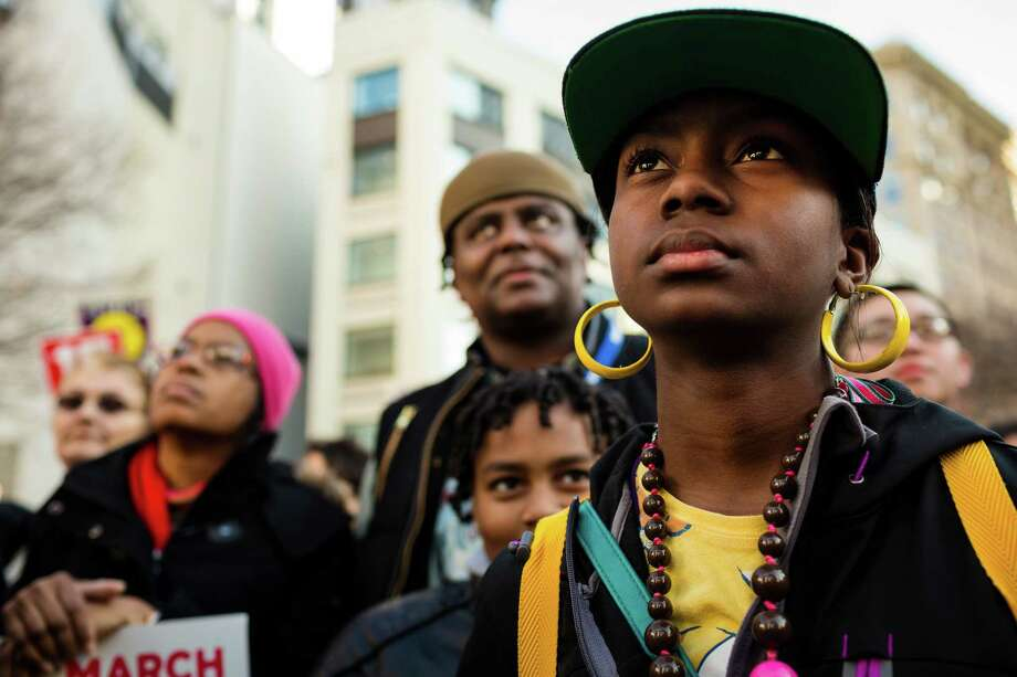 Graciela jones, 11, right, listens to speakers present following the 32nd ÒRise Up!  Restore the Dream!Ó annual celebration for Martin Luther King, Jr., on Monday, Jan. 20, 2014, in Seattle. A mass of hundreds walked from Garfield High School to Westlake Park. The event also included a rally and a workshop. Photo: JORDAN STEAD, SEATTLEPI.COM / SEATTLEPI.COM