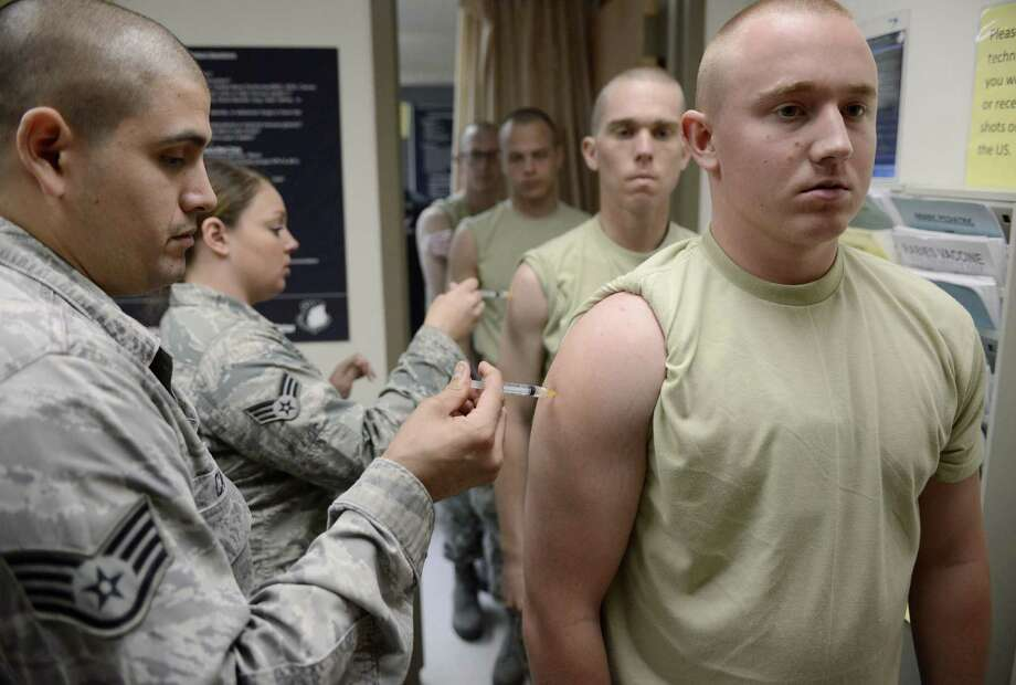 Staff Sgt. Stephen Carreon administers the rabies vaccine to Airman Kevin Danaher at Wilford Hall Ambulatory Surgical Center. Photo: Photos By Darren Abate / For The San Antonio Express-News