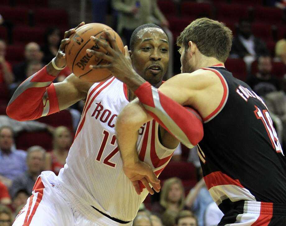 Joel Freeland of the Trail Blazers tries to defend Rockets center Dwight Howard. Photo: Karen Warren, Houston Chronicle