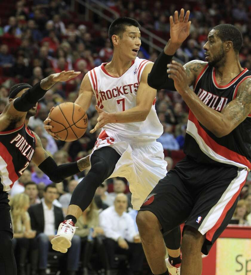 Rockets point guard Jeremy Lin looks to make a pass between LaMarcus Aldridge and Mo Williams of the Trail Blazers. Photo: Karen Warren, Houston Chronicle