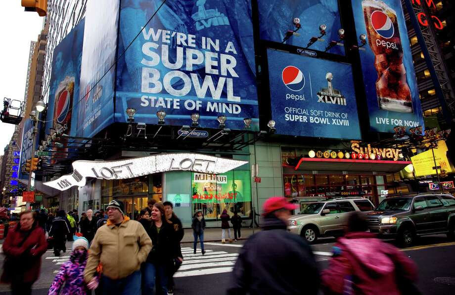 "Large signs advertising the Super Bowl are seen along Times Square, Monday, Jan. 20, 2014, in New York. Preparations for fan venues and activities for the upcoming Super Bowl are starting to appear along several blocks of Broadway, part of which has been dubbed ""Super Bowl Boulevard"". (AP Photo/Craig Ruttle) ORG XMIT: NYCR104 Photo: Craig Ruttle / FR61802 AP"