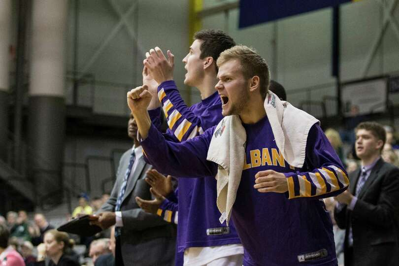 UAlbany players react from the sideline after their team takes the lead during the mens' basketball