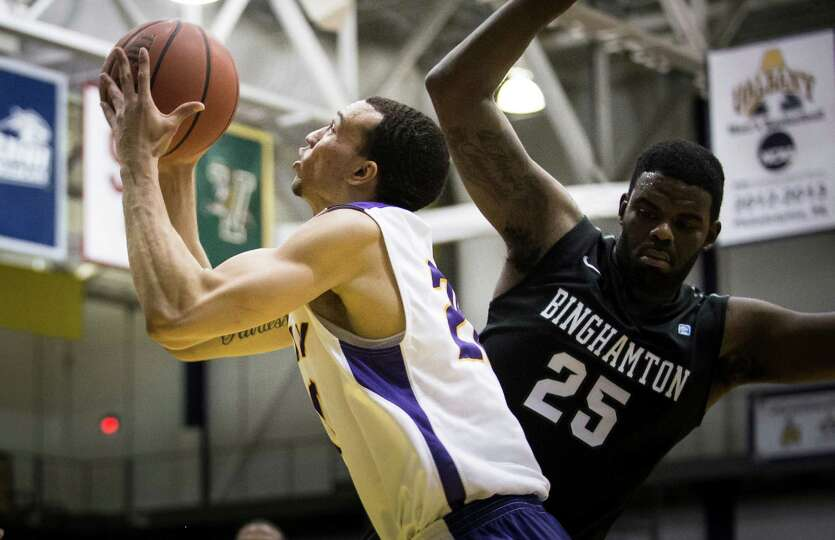 UAlbany's #20 Gary Johnson makes a shot attempt past Binghampton's #25 Roland Brown during the mens'