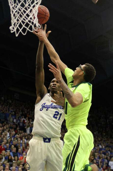 Kansas center Joel Embiid puts up a shot despite the defense of Baylor's Isaiah Austin. Embiid had 12 points; Austin finished with 16. Photo: Ed Zurga / Getty Images / 2014 Getty Images