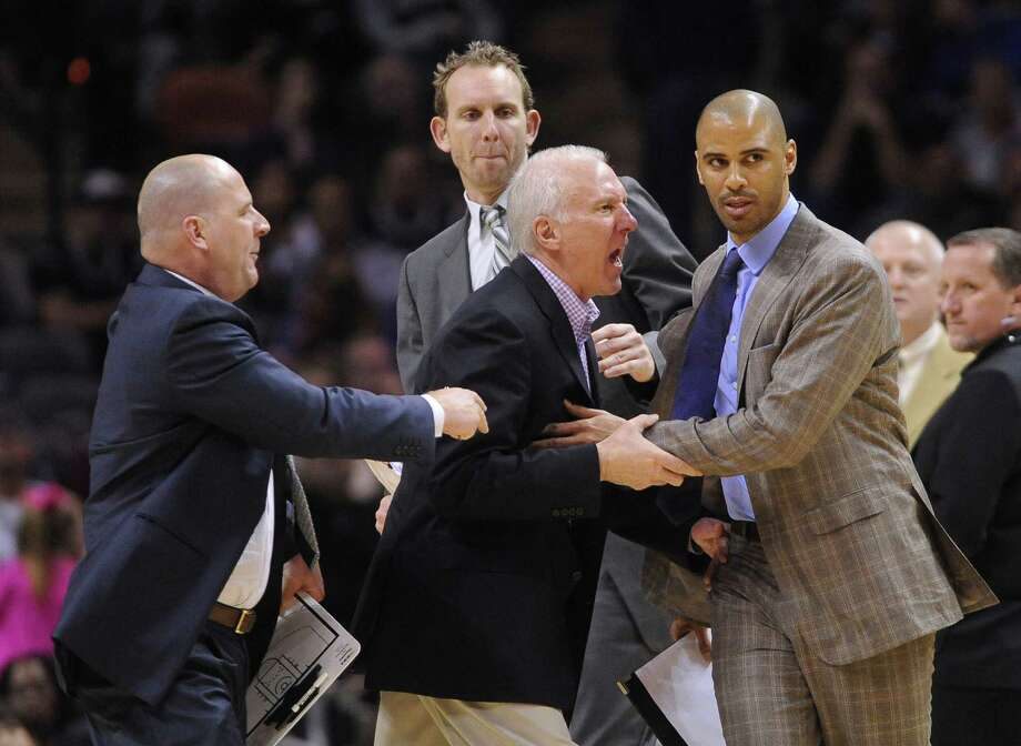 San Antonio Spurs coach Gregg Popovich, middle, is held back by assistant coaches Jim Boylen, left, Sean Marks, top, and Ime Udoka as he argues with officials during second-half NBA action against Portland in the AT&T Center on Friday, Jan. 17, 2014. The Trailblazers won, 109-100. Photo: San Antonio Express-News / San Antonio Express-News