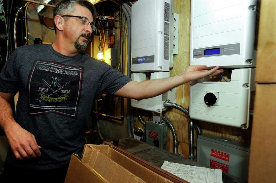 David Stout talks about the controls for the 40 photovoltaic solar panels that are in the basement of his family's Newtown home, Monday, January 20, 2014. Photo: Carol Kaliff / The News-Times