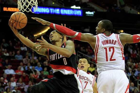 Trail Blazers guard Damian Lillard has the full attention of Rockets guard Jeremy Lin, left, and center Dwight Howard as he drives to the basket in the second half. Lillard committed four of the Blazers' 11 turnovers but scored 24 points on 7-for-17 shooting.