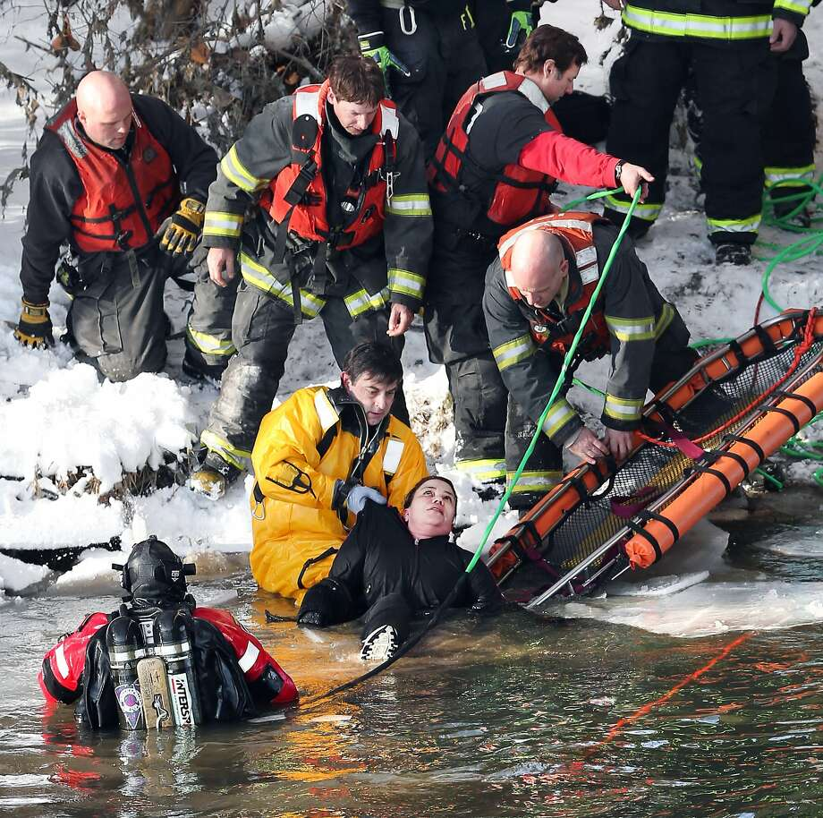 Indianapolis Fire Department Capt. Casey Sweeney hands off a woman who jumped off the 16th Street bridge into the White River to rescuers on shore, Monday, Jan. 20, 2014 in Indianapolis. The woman was taken to IU Health Methodist Hospital for treatment of hypothermia. (AP Photo/The Indianapolis Star, Matt Detrich)  NO SALES Photo: Matt Detrich, Associated Press