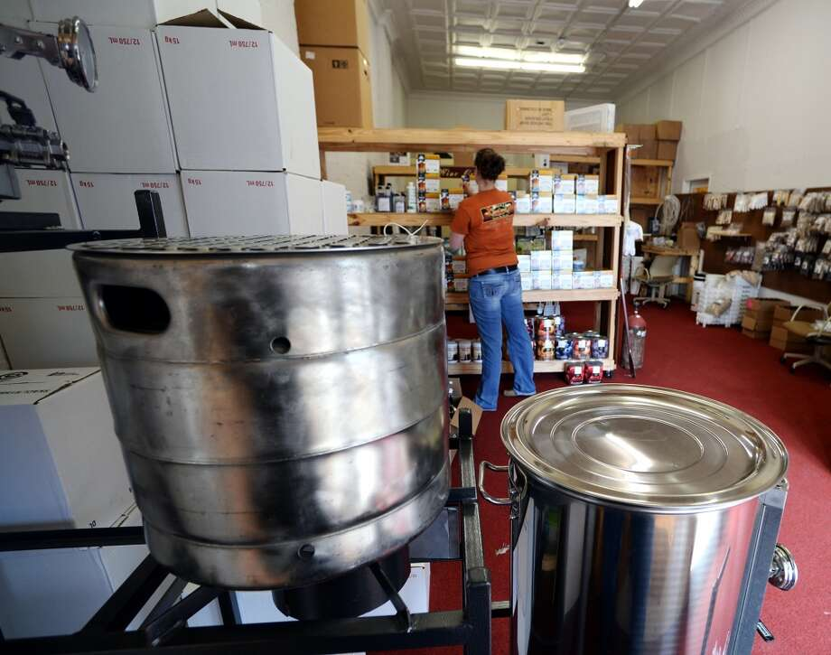 Manager Chelsie Abercrombie straightens brewing kits on the shelves of the Brew Shop on Tuesday afternoon. Abercrombie said that Christmas really cleaned out a lot of their merchandise, but that they expected a fresh shipment soon. The Brew Shop in Beaumont caters to home brewers and wine fermenters.  Photo taken Tuesday, 1/7/14 Jake Daniels/@JakeD_in_SETX