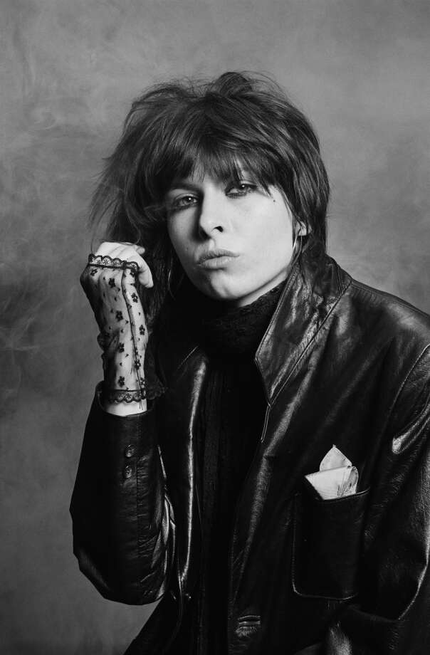 Chrissie Hynde, singer and guitarist with rock band The Pretenders, wearing black lace fingerless gloves and a black leather jacket in a studio portrait, against a smoky background, United Kingdom, circa 1979. Photo: Fin Costello, Redferns