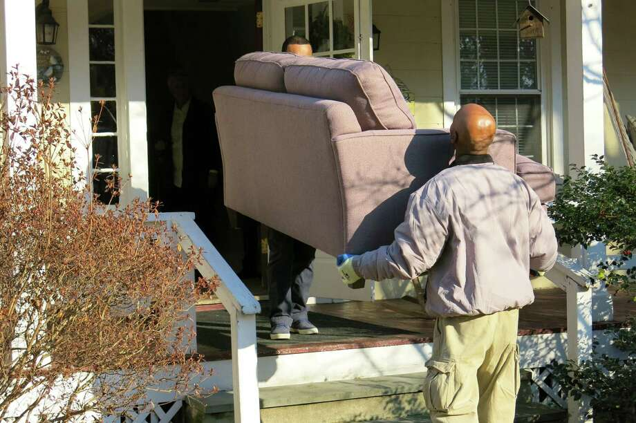 A Bassett Furniture crew carries a sofa into the Project Return group home on Compo Road last Friday. The furniture chain, which recently opened a store on Post Road East, donated $10,000 worth of new furnishings to the group home, which houses adolescent girls who are in crisis. Photo: Contributed Photo / Westport News