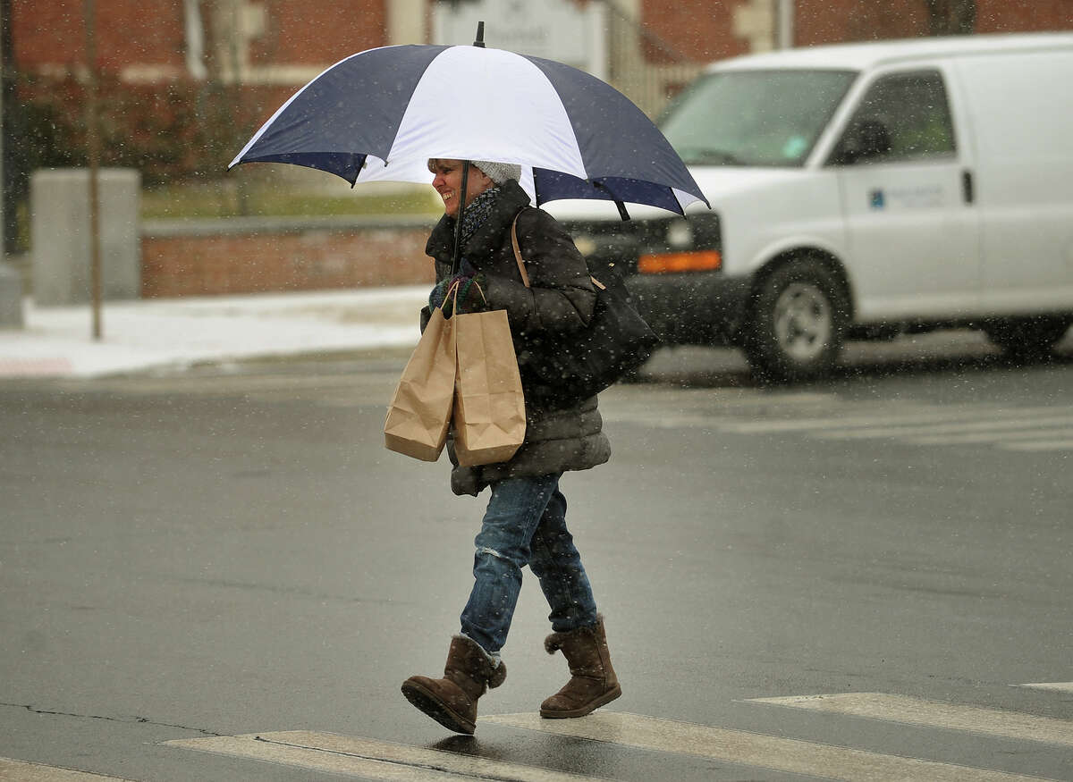 A pedestrian crosses the Post Road in Fairfield, Conn. during the start of the snowstorm on Tuesday, January 21, 2014.