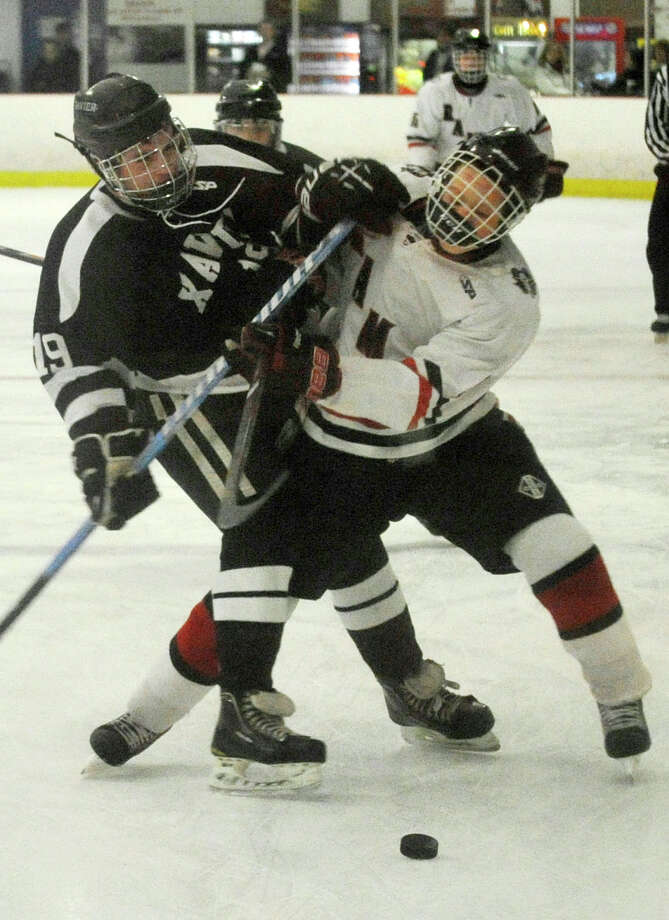 Xavier's Bryan Stanton and New Canaan's Davis Bruch collide during their hockey game at Darien Ice Rink in Darien, Conn., on Monday, Jan. 20, 2014. New Canaan won, 5-2. Photo: Jason Rearick / Stamford Advocate