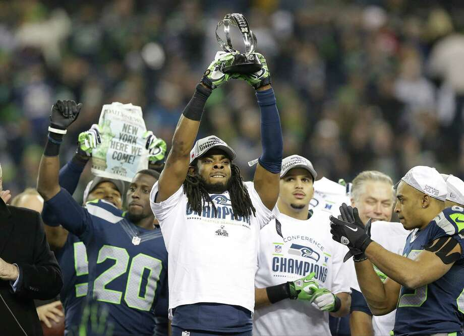 Seattle Seahawks' Richard Sherman holds up the George Halas Trophy after the NFL football NFC Championship game against the San Francisco 49ers Sunday, Jan. 19, 2014, in Seattle. The Seahawks won 23-17 to advance to Super Bowl XLVIII. Photo: Elaine Thompson, AP / AP