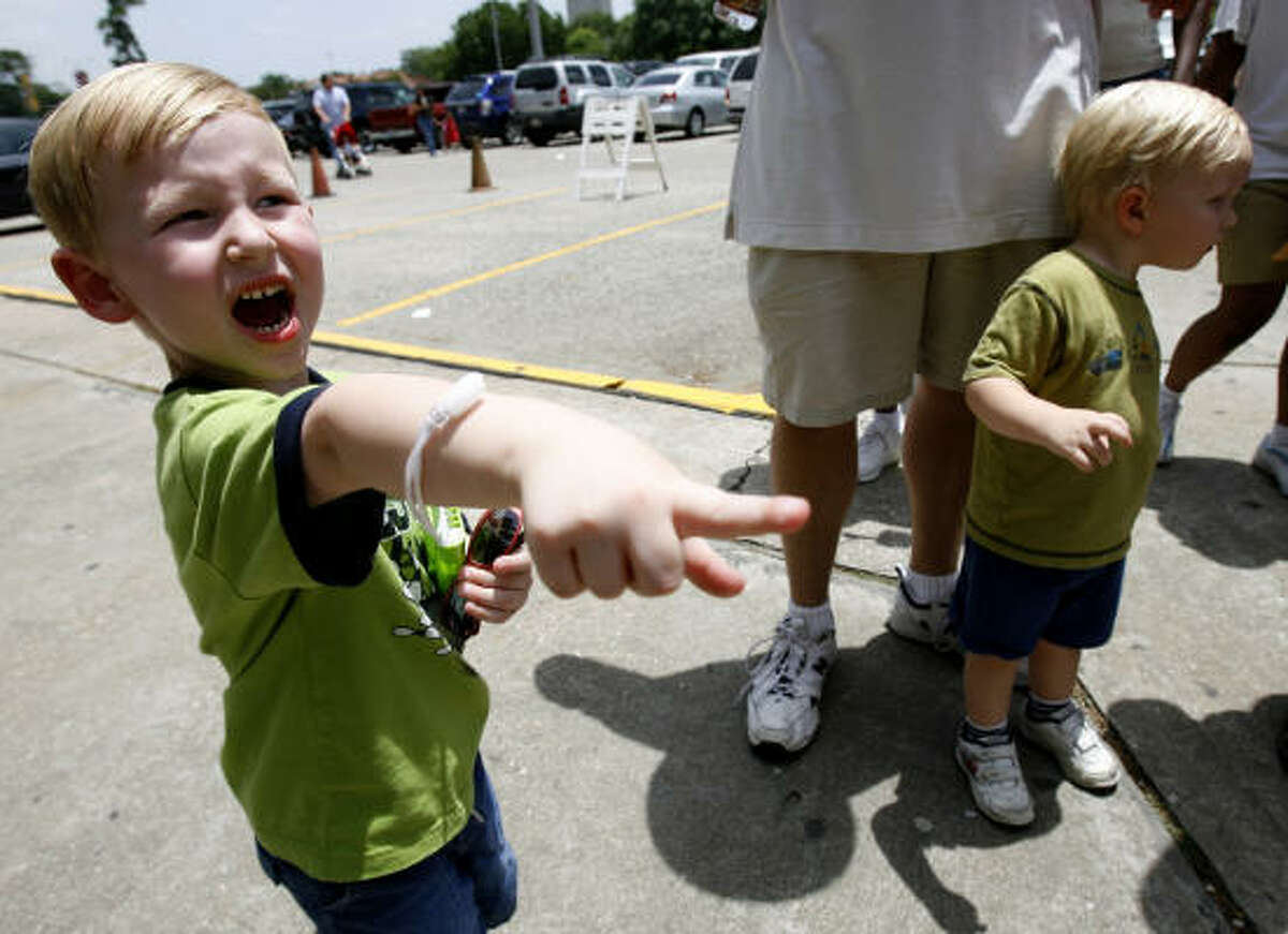 Drew Keady, 4, of Grapevine, yells out that he sees the Hermann Park train approaching the station, as he and his cousin, Carter Jones, 2, wait their turn in line for a ride.