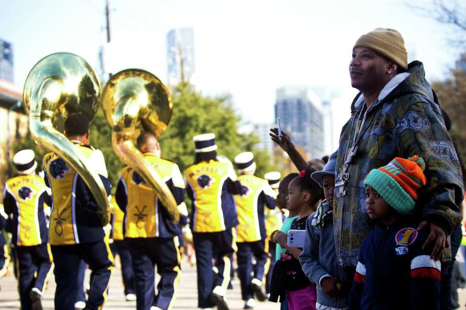 Landis Robinson, center, watches the marching bands down San Jacinto Street with his sons Lance Robinson, 5, and Xavier Robinson, 6, at the 20th Annual MLK Grande Parade, Monday, Jan. 20, 2014, in Houston. Photo: Marie D. De Jesus, Houston Chronicle / © 2014 Houston Chronicle