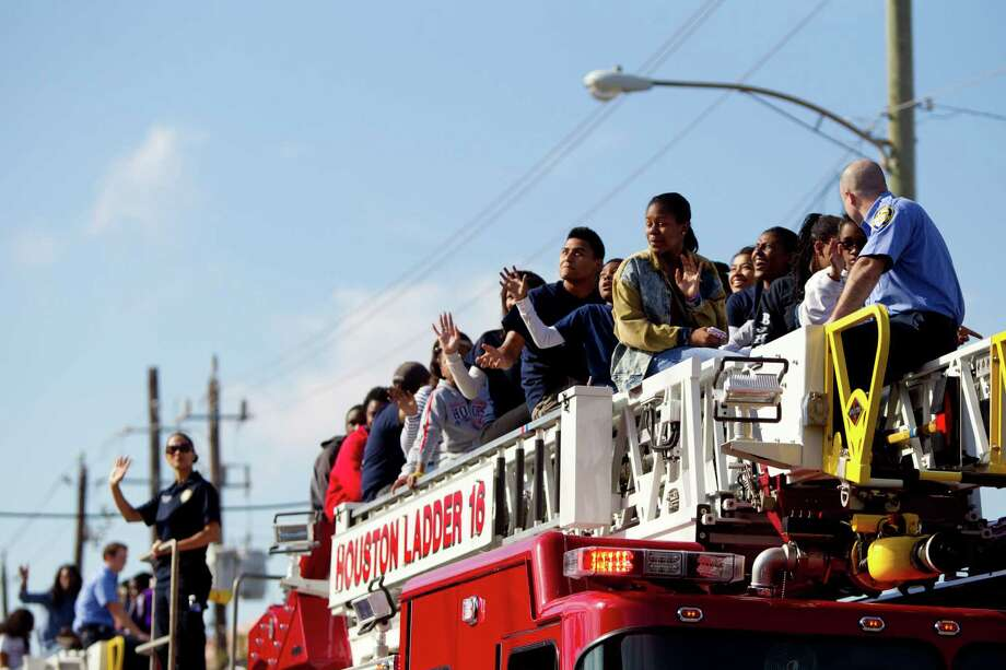 The Houston Fire Department gives members of the audience a ride along with firefighters on a fire truck during the 20th Annual MLK Grande Parade, Monday, Jan. 20, 2014, in Houston. Photo: Marie D. De Jesus, Houston Chronicle / © 2014 Houston Chronicle