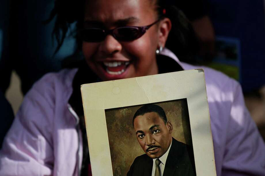 A young parade watcher holds a portrait of civil rights leader at 36th annual Dr. Martin Luther King, Jr. Birthday Parade, Monday, January 20, 2014, in Houston, Texas. Photo: Johnny Hanson/Houston Chronicle
