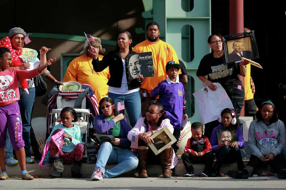 People along the parade route hold photos and wave flags celebrating Dr. Martin Luther King, Jr. birthday, Monday, January 20, 2014, in Houston, Tx. Photo: Johnny Hanson/Houston Chronicle