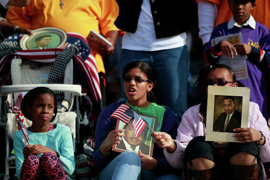 Three young girls watching MLK parade hold photos and wave flags celebrating Dr. Martin Luther King, Jr. birthday, Monday, January 20, 2014, in Houston, Tx. Photo: Johnny Hanson/Houston Chronicle
