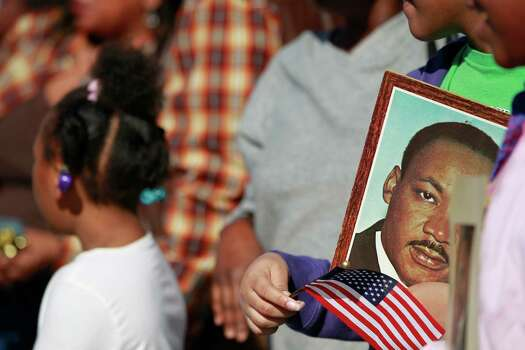 "Many people along the MLK parade route were holding portraits and waving flags honoring the civil rights leader. The ""Original"" 36th annual Dr. Martin Luther King, Jr. birthday parade was held today near Minute Maid Park. Photo: Johnny Hanson/Houston Chronicle"