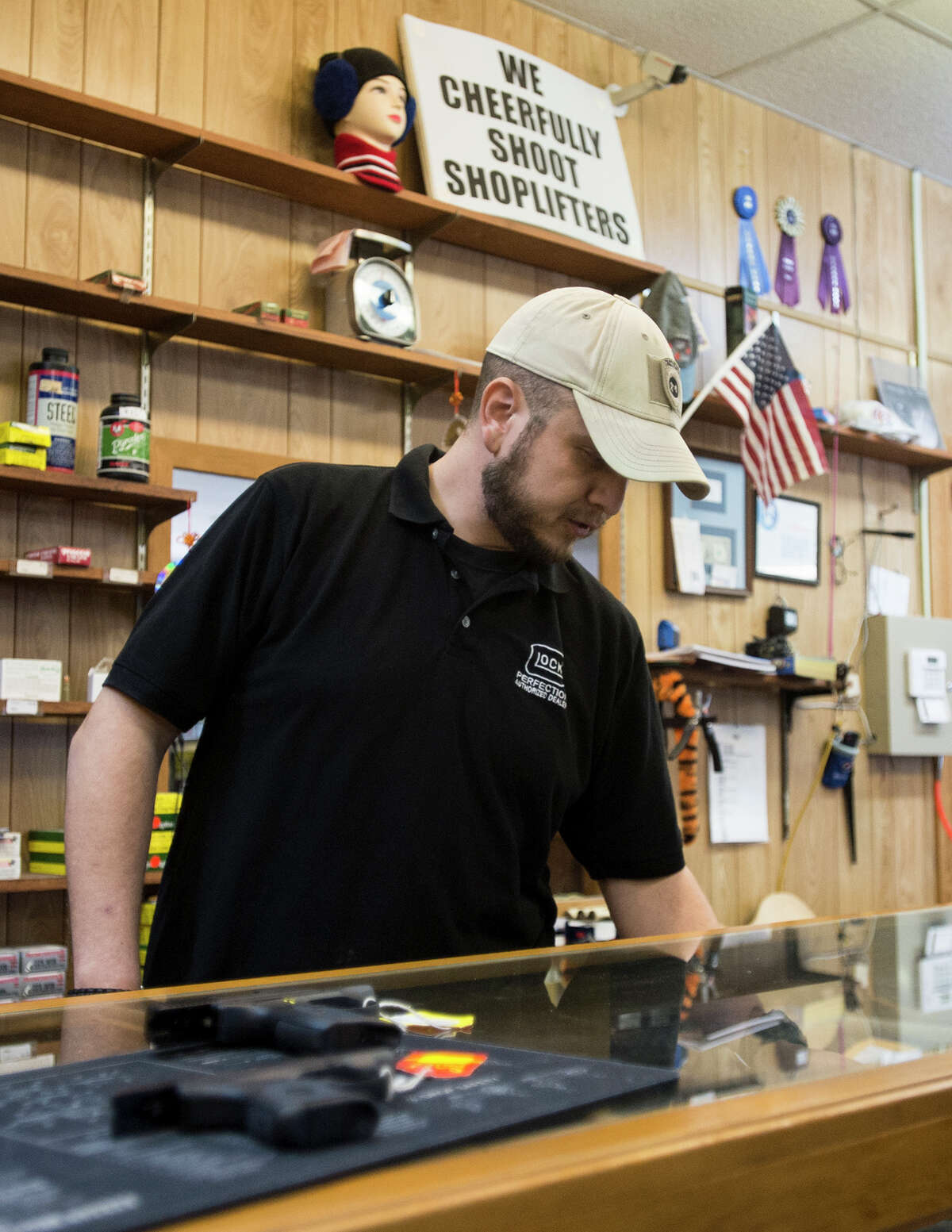 John Troquille of Onpoint CHL talks about their bestselling handguns at Ray's Pawn Shop in Bridge City on Friday afternoon. Troquille, a Beaumont native currently living in Bridge City, started up his concealed handgun license class three years ago. Photo taken Friday, 1/17/14 Jake Daniels/@JakeD_in_SETX