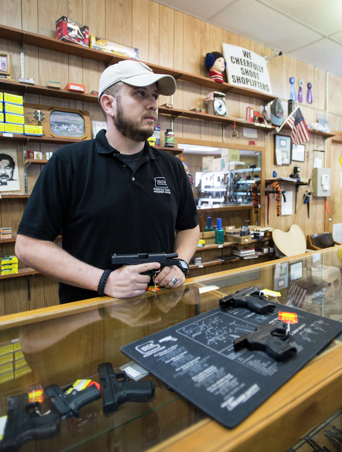John Troquille of Onpoint CHL talks with a customer about handguns at Ray's Pawn Shop in Bridge City on Friday afternoon. Troquille, a Beaumont native currently living in Bridge City, started up his concealed handgun license class three years ago. Photo taken Friday, 1/17/14 Jake Daniels/@JakeD_in_SETX