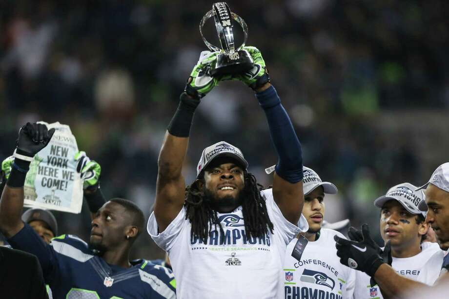 Seattle Seahawks player Richard Sherman hoists the NFC Championship trophy after the Seahawks defeated the San Francisco 49ers to advance to the Super Bowl at CenturyLink Field on Sunday, January 19, 2014. Photo: JOSHUA TRUJILLO, SEATTLEPI.COM / SEATTLEPI.COM