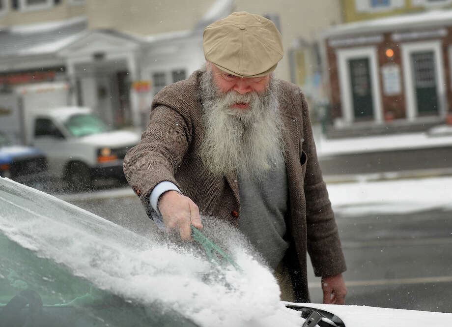 Doug Munson of Fairfield clears snow from his windshield in downtown Fairfield, Conn. during the start of the snowstorm on Tuesday, January 21, 2014. Photo: Brian A. Pounds / Connecticut Post