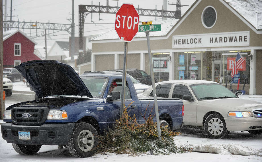 A pickup truck sits collided with a stop sign after being involved in a two car accident at the intersection of Bungalow Avenue and the Post Road in Fairfield, Conn. during the snowstorm on Tuesday, January 21, 2014. Photo: Brian A. Pounds / Connecticut Post