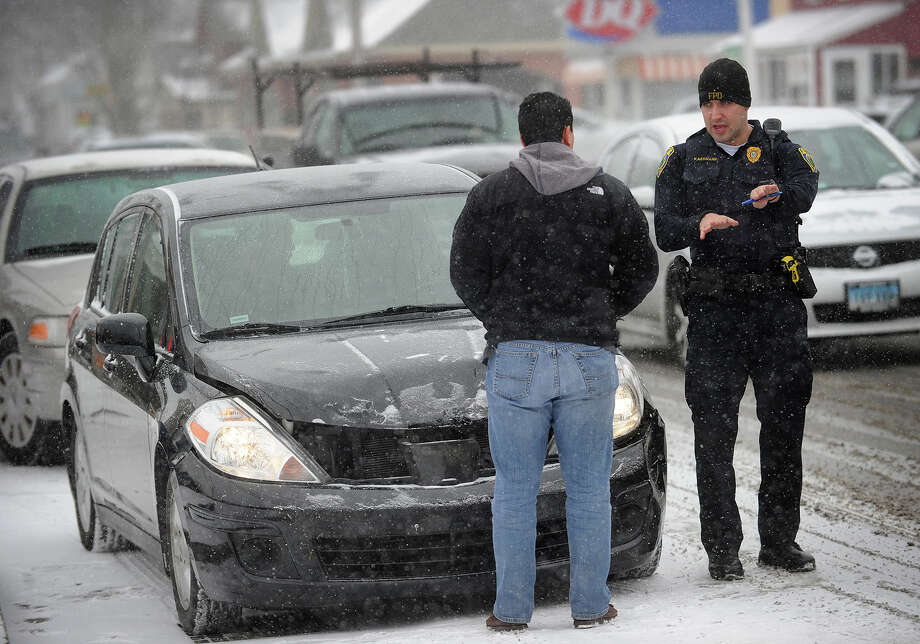 A Fairfield police officer talks with a man involved in a two car accident at the intersection of Bungalow Avenue and the Post Road in Fairfield, Conn. during the snowstorm on Tuesday, January 21, 2014. Photo: Brian A. Pounds / Connecticut Post