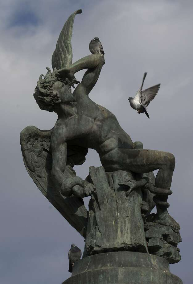 Tormented devil: A pair of pigeons cause Satan to recoil in horror in Retiro Park in Madrid. The bronze 