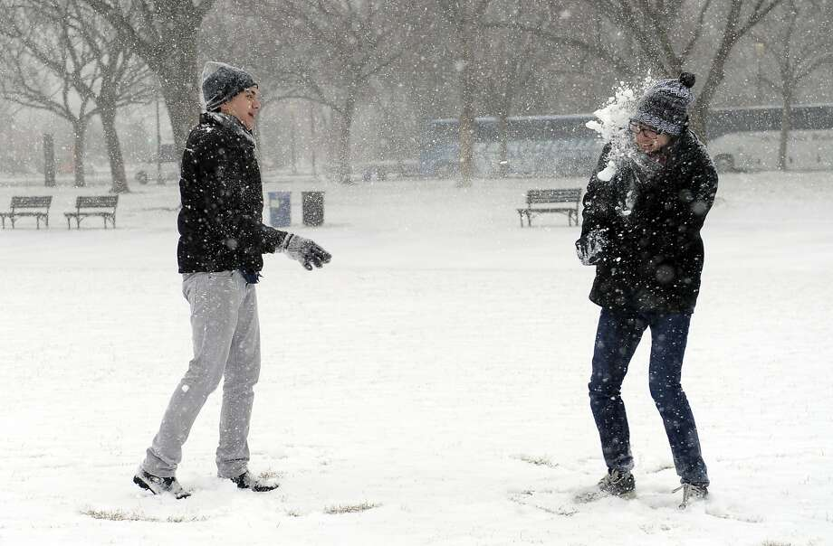 Bull's-eye! Jeff Scott scores a direct hit on his pal Rick Mendenhall at the National Mall in Washington as a major storm dumps several inches of snow in the nation's capital. Photo: Susan Walsh, Associated Press
