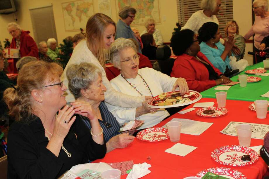 Maddie DuBois, a member of The Woodlands High School Lady Highlanders Soccer Team, serves cookies to seniors during a holiday party hosted by team members at the Copperwood Senior Apartment Complex on Dec. 17. Photo: The Woodlands High School