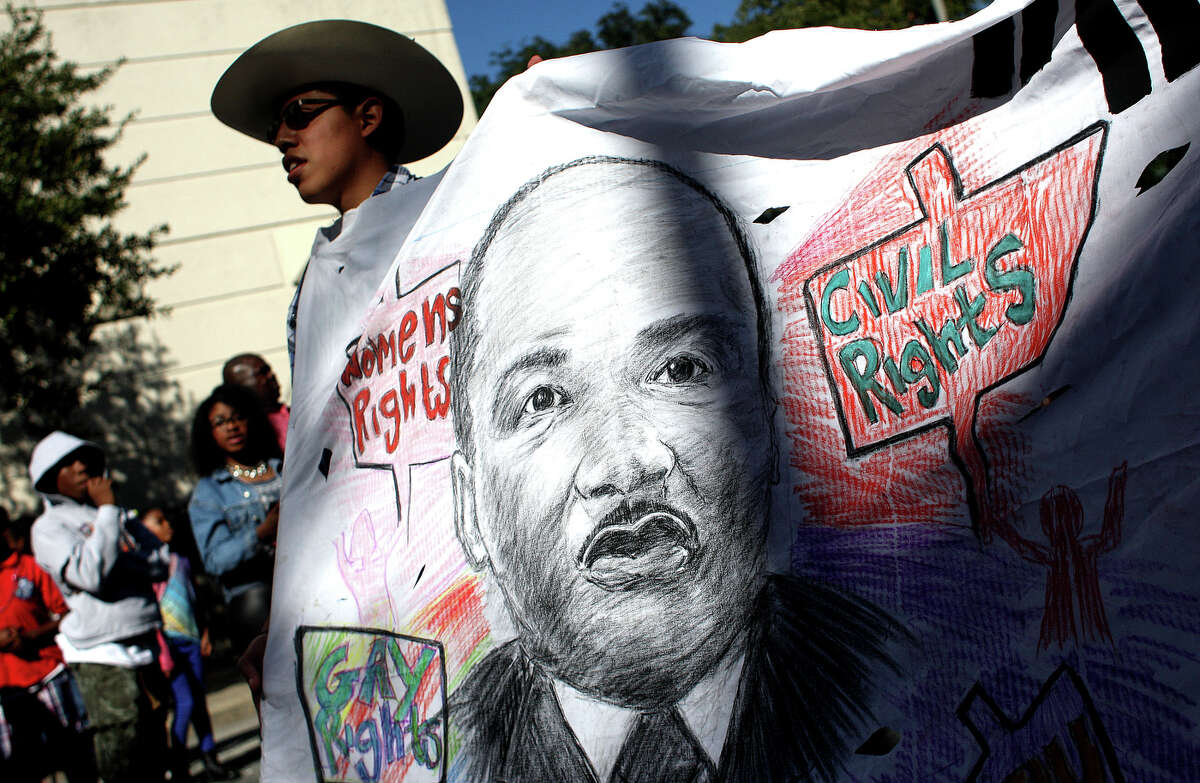 Steven Arteaga, 18, holds a banner walking with representatives from the Service Employees International Union during the Black Heritage Society's 36th Annual Original Martin Luther King Jr. Parade downtown Monday, Jan. 20, 2014, in Houston.